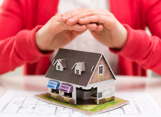 Closeup of female realtor hands showing house model to client.