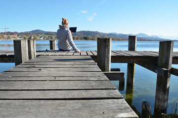 Girl reading from a tablet on the wooden jetty against a lake.