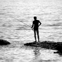 Fisherman on a reef silhouette