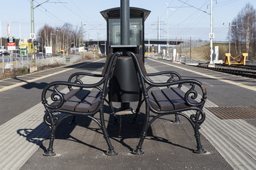 A couple of benches on an empty train station on the platform.