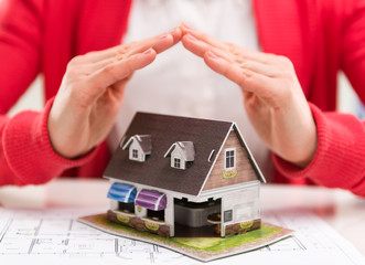 Close-up of mortgage agent with family house model in agency