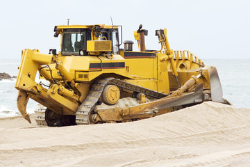 yellows excavators on the city  beach working sand moving