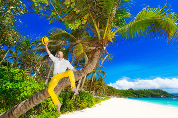 Happy man in yellow trousers and white shirt sitting on a palm