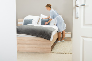 Young Maid Arranging Pillow On Bed