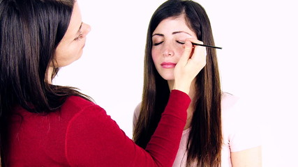 Female makeup artist at work with fashion model.
