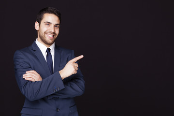 Handsome business man pointing at something against dark backgro