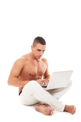 Caucasian man with naked chest working with notebook on the floo
