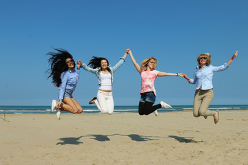 active girls jumping on beach on sunny day