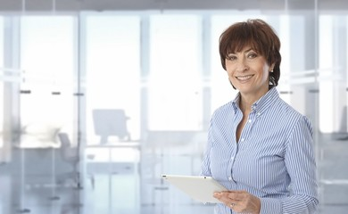 Mid-adult businesswoman using tablet computer