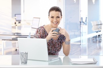 Happy woman at office desk