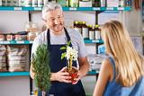 Fototapety Mann in Gärtnerei verkauft Blumen