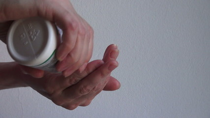 Woman hands taking pill from the bottle
