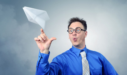 Business man in glasses throwing a paper plane