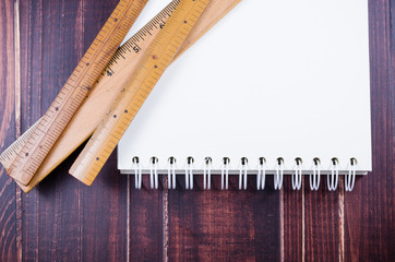 Wooden ruler and notebook on wooden board background