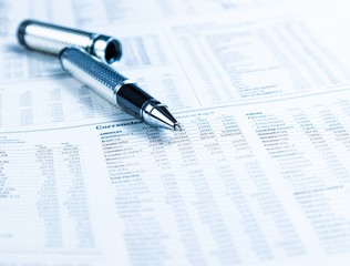 financial business pen on currencies newspaper
