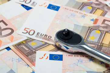 Euro banknotes and wrench