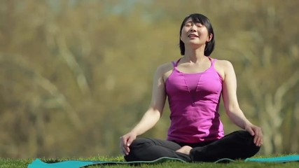 Young Asian woman fitness in a park yoga meditation