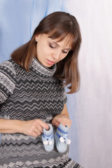 Pregnant woman holding blue booties