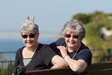 Playful elderly twin sisters on holiday by the ocean