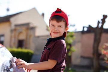 Little preschooler boy wash car outdoor