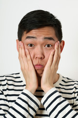 Astonished young Asian man covering his face with palms