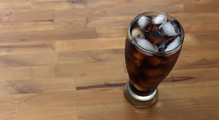 Glass of pop with ice on wooden table
