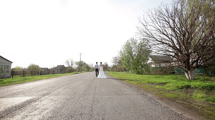 bride and groom are on the road away