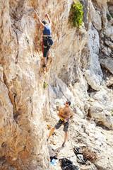 Senior woman lead climbing, guy belayer watching her
