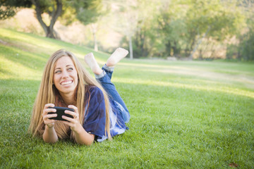Smiling Young Woman Using Cell Phone Outdoors