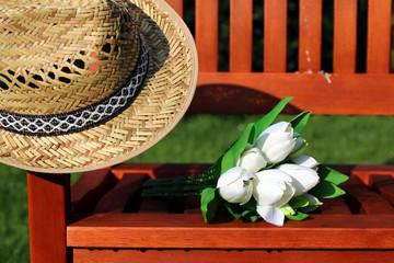 Strohhut, Strauß Tulpen auf Holzbank