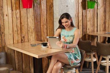 Attractive young woman using tablet in restaurant
