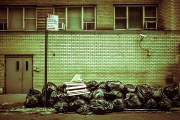 Toxic toned image of pile of plastic trash bags on curb