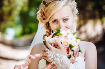 Beautiful bride outdoors. Bride holding wedding bouquet outside