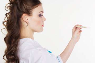 Pretty young female doctor with thermometer