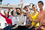 Excited students with arms outstretched outdoors