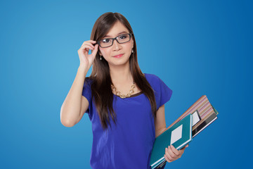 Young teacher adjusting her glasses while holding books