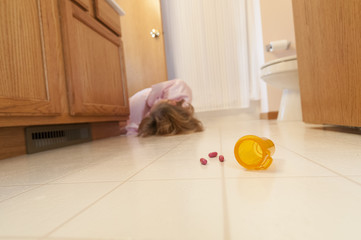 Woman on bathroom floor with pills and bottle