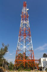 Telecommunication tower with antennas against blue sky