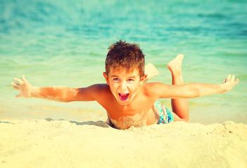 Summer holidays. Joyful boy having fun at the beach