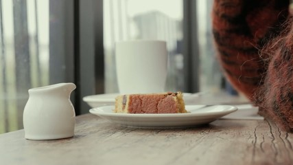 Woman eating cake and drinking tea by window in cafe
