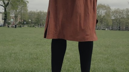 Woman standing in a park with her skirt blowing in the wind