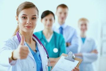 Young happy female doctor showing thumbs up