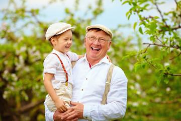 happy grandfather and grandson having fun in spring garden