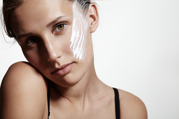 beauty young girl with a white cream on a cheek