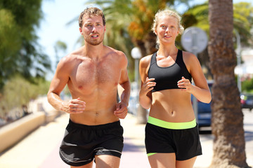 Sport people - active couple running in city