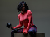 Woman with black hair holding dumbell