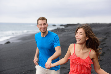 Happy couple laughing together walking on beach