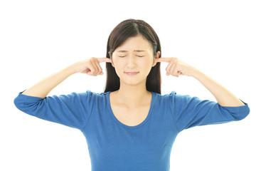 耳を抑える女性