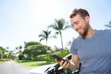 Car and smartphone app - man texting sms on phone
