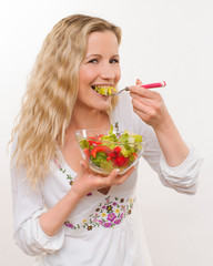 Young housewife eating salad